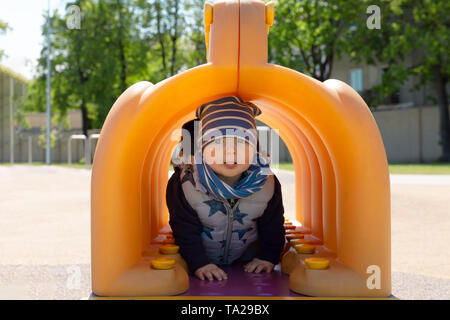 Child playing in playground, walking trough tunnel - Stock Photo