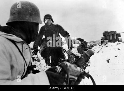 German soldiers take cover in a ditch from enemy artillery fire. They are supported by a Panzerwagen VI Tiger. Photo of the Propaganda Company (PK): war correspondent John. - Stock Photo