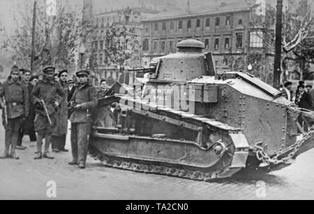 A group of Spanish national supporters (on the left in mixed uniforms) posing in front of a beaverette armed with an automatic cannon (French model Renault FT17, belonging to the Spanish infantry) in the center of Zaragoza, Aragon, Spain. In the background, passers-by. The Republicans tried to invade Zaragoza in vain in July, 1936. A further offensive failed in September, 1937. - Stock Photo