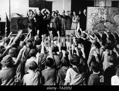 In a elementary school classroom, decorated with world war propaganda posters, a swastika flag and a map with the territories separated due to the Treaty of Versailles, teachers and students honor a 'national celebration' with singing the German national anthem and the Horst Wessel Lied (song), as well as the Hitler salute. - Stock Photo