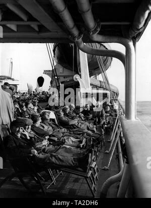 Vacationers are sunbathing on deck chairs on board a cruise ship of the Nazi organization 'Kraft durch Freude' ('Strength through Joy') . - Stock Photo