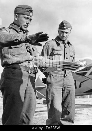 Photo of a captain (left), who is explaining his attack to a lieutenant (right) with a map. Both officers are wearing leather flight suits. - Stock Photo