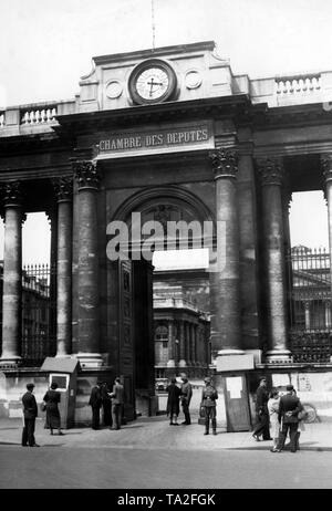Entrance gate of the Palais Bourbon in Rue Universite. German soldiers stand guard at the gate and control the entrants. - Stock Photo