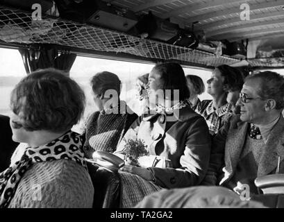 Vacationers of the Nazi organization 'Kraft durch Freude' ('Strength through Joy') on a boat. Undated photo. There is a typewriter in the hand luggage storage place. - Stock Photo