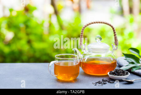 Tea in glass cup and teapot on summer outdoor background. Copy space. - Stock Photo