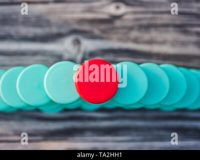 Image of different colored plastic caps on wooden background