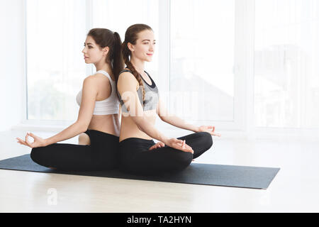 Two attractive women in sportswear on white background doing yoga - Stock Photo