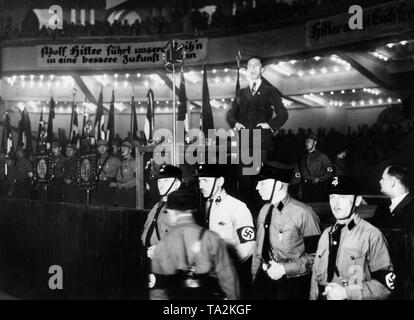 Joseph Goebbels holds a campaign speech at the Berlin Sports Palace during the Reichstag election campaign of 1932. Before him stands a group of SS men as personal stewards. The slogans on the banners read: 'Adolf Hitler leads our ranks into a better future ...' and 'Hitler makes you free'. - Stock Photo