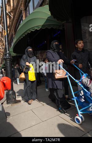 Women from the middle-east wearing full burqua outside Harrods, the famous London department store, Knightsbridge, London. /  Frauen aus dem Nahen Ost - Stock Photo