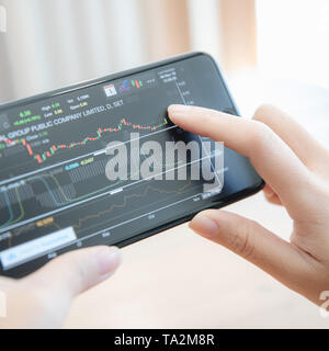 Female hand with smartphone trading stock online in coffee shop , Business concept - Stock Photo