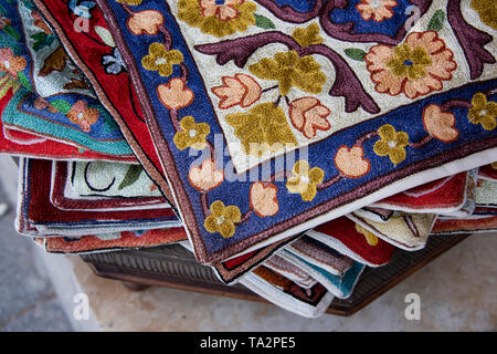 Oman, capital city of Muscat, Muttrah Souk. Ornately embellished embroidered pillow cases on display at historic marketplace or souk. - Stock Photo