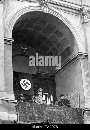 Adolf Hitler speaks to Memel Germans from the balcony of the City Theater during a rally in the town square after the annexation of Memel. Left, Wilhelm Frick, at right Ernst Neumann. - Stock Photo