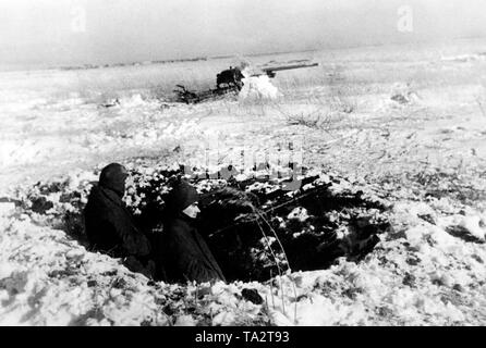 Soldiers stand in a dug fighting stand in a position ahead of Moscow in the area of Army Group Center with MG34 machine gun. In the background, an anti-tank cannon. - Stock Photo