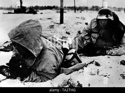 Two Waffen-SS men take cover from enemy missiles. Presumably, they are located south of Lake Ladoga in the northern section of the Eastern Front. Photo of the Propaganda Company (PK): war correspondent Raudies. - Stock Photo