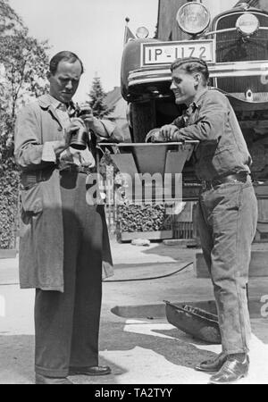 Two men examine the pistons and connecting rods of a car. The jacked-up car has a license plate of the province Schleswig-Holstein. - Stock Photo