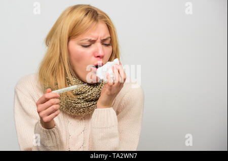 Girl in scarf hold thermometer and tissue close up. Cold and flu remedies. Take temperature and assess symptoms. Measure temperature. High temperature concept. Woman feels badly ill sneezing. - Stock Photo
