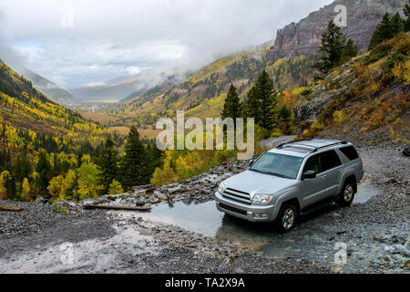 Rainy Day on Mountain Trail - A SUV's driving through a mountain creek on rugged Black Bear Pass trail, near Telluride, CO, USA. - Stock Photo