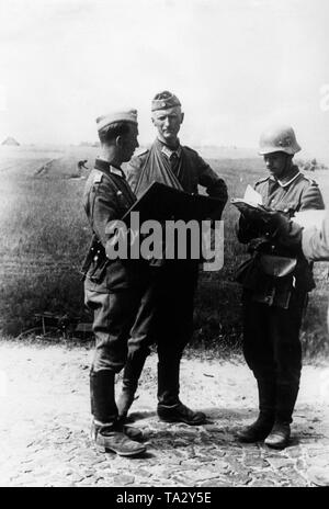 In the middle a wounded officer, on the right a lieutenant who takes notes. Photo: war correspondent v. Kuegelgen. - Stock Photo