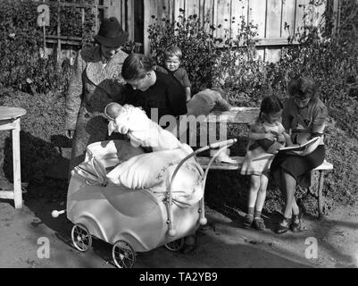 The leader of the NSF Kreisfrauenschaft (women's aid agency) visits evacuated families  before the bomb war. Here, a mother is showing her fifth child born in East Prussia. - Stock Photo