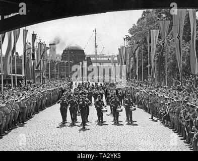 Photo of a marching band of the Condor Legion on their way to Karl Muck Platz (now Johannes Brahms Platz) shortly after the arrival of the troops at the gangway (in the background, St. Pauli) of the Port of Hamburg on May 30, 1939. They are carrying the Turkish crescent donated by General Francisco Franco. On the right and left side of the road, SA men and spectators have lined up. - Stock Photo