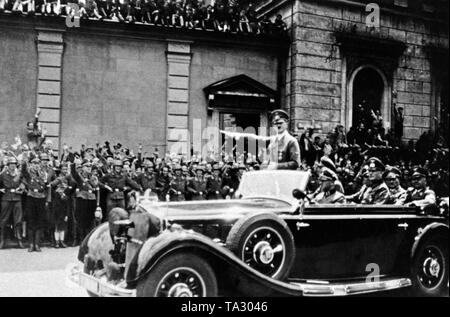 Adolf Hitler in the car on his way to his private apartment after greeting Benito Mussolini in Munich. Also in the car, the driver Erich Kempka, Wilhelm Keitel, Franz Ritter von Epp and Adolf Wagner. In the background the wall to the courtyard garden of the Residenz on Odeonsplatz. - Stock Photo