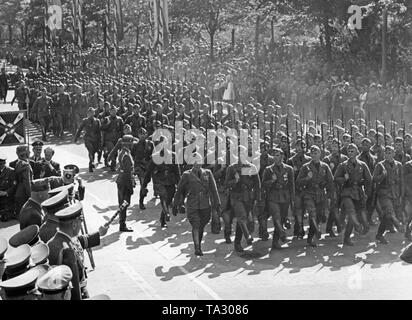 Photo of a unit of the ground troops (Group Beekeeper) of the Condor Legion at the victory parade at Karl Mack Platz after the arrival of the Legion in the Port of Hamburg on May 30, 1939. Spectators have lined up on the right and left of the roadside. On the right below (hidden, general's baton), Field Marshal General Hermann Goering greets the troops. - Stock Photo