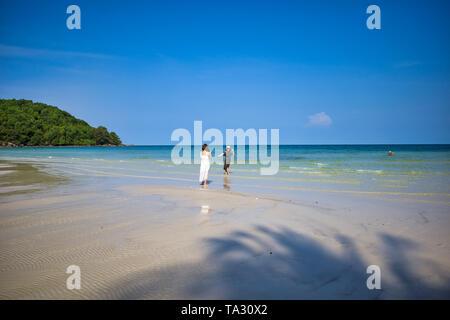 Phu Quoc island, Vietnam - March 31, 2019: White sand beach, sea horizon. Calm sea and girls walking on the beach. Coast of the South China Sea - Stock Photo