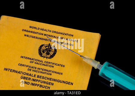 Vaccination requirement should be vaccinated Syringe with needle on a vaccination book - Stock Photo