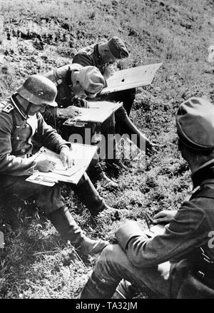A regimental command staff is working outdoors. Short lines of communication were essential for the command posts of the Wehrmacht. in the picture officers interpret messages from the front and write reports for the leadership. Left in the picture is sitting an Oberfeldwebel (master sergeant). Photo: war correspondent Ulrich. - Stock Photo