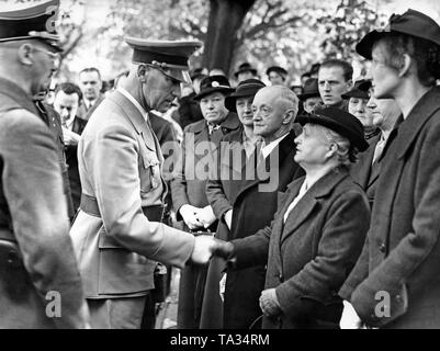 Reich Minister of the Interior Wilhelm Frick (shaking hands) welcomes the relatives of those, who were shot dead by the Czech army in 1919 in the cemetery of Kadan on October 19, 1938. - Stock Photo