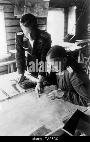 The Luftwaffe Forward Air Controller (left), here a lieutenant, presents a general staff officer, here a colonel, aerial photographs of the reconnaissance. The picture was taken at Gurodez, September 1941, on the eastern front. Photo: war reporter Ulrich. - Stock Photo
