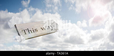 Crossroad signpost saying this way concept for lost, confusion or decisions in the blue sky - Stock Photo