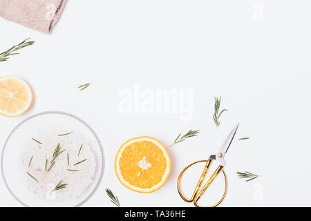 Homemade aromatic bath sea salt with rosemary and fresh citrus lemon and orange, flat lay composition on white background with copy space. - Stock Photo