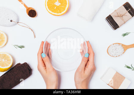 Woman's hands holding empty glass bowl to make homemade bath body scrub of coffee, sea salt with rosemary and fresh citrus lemon and orange, flat lay  - Stock Photo