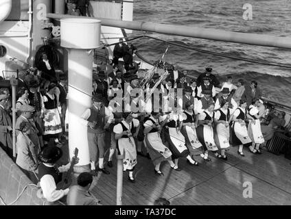 During a sea voyage to Madeira, a group of vacationers from Winningen/Mosel are dancing in Palatinate costumes on the stern of the cruise ship 'St. Louis' that belonged to the Nazi organization 'Kraft durch Freude' ('Strength through Joy'). - Stock Photo