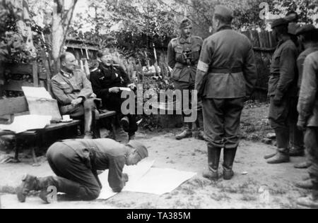 Russian prisoners are interrogated by officers of the Wehrmacht on the eastern front near Panjewitsch. Sitting on the bench, a staff officer and an officer of the Panzertruppe, on the left soldiers of the Red Army. Photo: war reporter Tannenberg. - Stock Photo