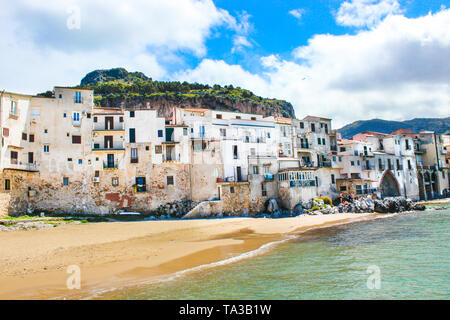 Traditional historical houses on the coast of Tyrrhenian sea in Sicilian Cefalu, Italy. Behind the houses there is rock overlooking the city. The beautiful Italian city is popular tourist attraction. - Stock Photo