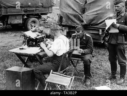 Members of a communication unit of the Wehrmacht on the Eastern front. A soldier typs commands on a typewriter. Two officers of the Luftwaffe in the rank of lieutenant provide information. Photo: war reporter Luden. - Stock Photo