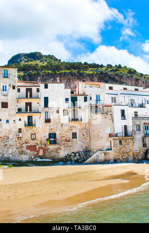 Beautiful old houses overlooking the Tyrrhenian sea in Cefalu, Sicily, Italy. Captured on vertical picture with rock behind the historical city. Cefalu is a popular vacation destination. - Stock Photo
