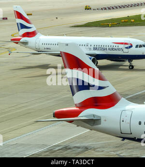 LONDON GATWICK AIRPORT, ENGLAND - APRIL 2019: Tail fin of a British Airways jet at Gatwick Airport with another of the airline's planes in the backgro - Stock Photo