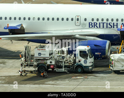 LONDON GATWICK AIRPORT, ENGLAND - APRIL 2019: Menzies Aviation fuel truck alongside a British Airways jet at Gatwick Airport - Stock Photo
