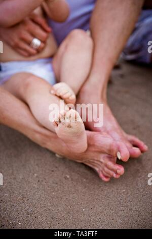 Dirty baby feet with beach sand, after playing with the waves and the sea in summer. - Stock Photo