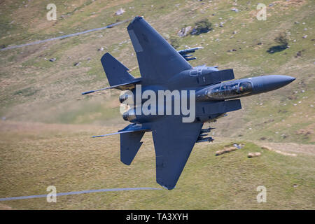 A USAF F-15 Strike Eagle passes through Mach Loop during low level training. - Stock Photo