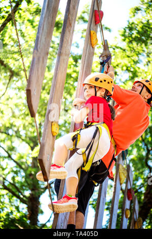 Little brave caucasian girl at outdoor treetop climbing adventure park. 7 years old girlie overcome obstacles on the rope path in the air - Stock Photo