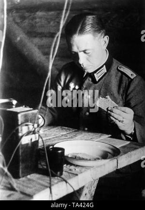 A lieutenant in the army, duty officer at work during the Battle of Moscow. He is eating a slice of bread between phone calls with the front and drawing of reconnaissance results. Photo: war correspondent Sepp Jaeger - Stock Photo