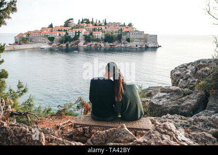 A young couple of tourists admires the beautiful view of the sea and the island of Sveti Stefan in Montenegro. - Stock Photo