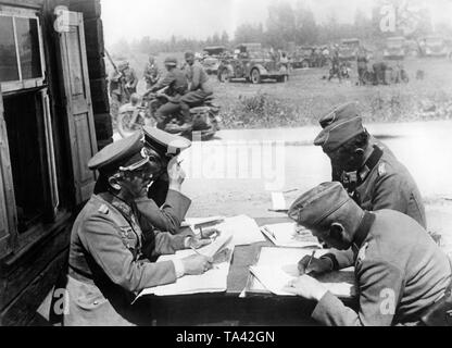 Officers and generals of the Wehrmacht in Lithuania during a briefing of the division command post. In the background dispatch riders and vehicles of the divison. Photo: war correspondent Zoll. - Stock Photo