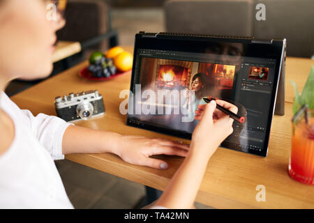 Freelancer retoucher woman works on convertible laptop computer with photo editing software using stylus. Photographer or designer performing digital  - Stock Photo