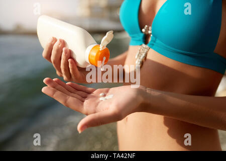 Woman hands putting sunscreen from a suntan cream bottle. Caucasian female squeeze suncream on her hand. Tanned girl wearing blue bikini swimsuit on t - Stock Photo