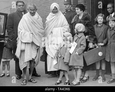 The leader of the Indian nationalist movement Mahatma Gandhi is invited to America by the President of the Indian Nationalist Association in America, Salandra Ghose. Salandra's daughter Mariam hands Gandhi the invitation. On the right next to Gandhi is his secretary Madeleine Slade, called Mirabeth, beside Salandra Ghose and her daughters Mariam and Lilabati. This shot was taken in front of Kingsley Hall, a community center in East London. - Stock Photo